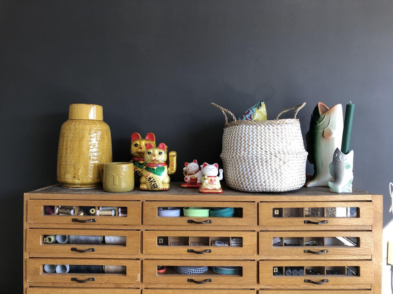 Winkekatzen und Vasen auf dem Vintage-Schubladenschrank