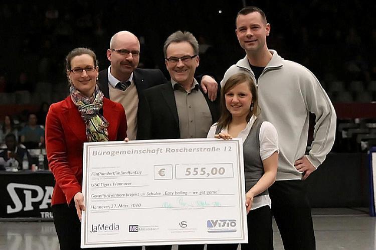 Michael Goch empfängt Spendenscheck von Vertretern der Roscherstraße 12
