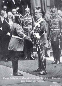 Die Generale Hans Georg von Plessen (Bildmitte) und Moriz von Lyncker (rechts) beobachten Kaiser Wilhelm II. und Otto von Emmich, den Kommandeur des X. Armee-Korps. Dritter von links ist der Stadtdirektor von Hannover, Heinrich Tramm. Anläßlich der Einweihung des Neuen Rathauses in Hannover wartet er geduldig, während der Kaiser zuerst den General Emmich begrüßt.